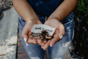 """An individual holds a handful of coins with a piece of paper that reads """"make a change"""" to encourage you to consider making a change in your own life by starting counseling or therapy with one of our mental health clinicians in the Colorado Springs, CO area!"""