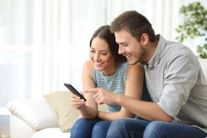 A couple smiles together while looking at a cell phone. They are feeling more connected after starting marriage counseling in Colorado Springs, CO with Altitude Counseling. They can get couples therapy or other help with online therapy in Colorado.