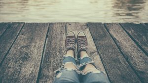 A teenager sits on a dock. They have started counseling for teens in Colorado Springs, CO with Altitude Counseling, online therapy in Colorado or online counseling for teens in Parker, CO.