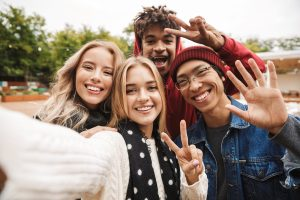 A group of four teenagers stand together smiling to take a selfie. They are much happier after starting counseling for teens in Colorado Springs, CO or in online therapy in Colorado with Altitude Counseling. You can get counseling for teens in Parker, CO for your teen therapy needs too!