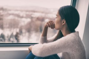 A young woman stares out the window looking anxious. She cannot wait to begin anxiety treatment in Colorado Springs, CO with Altitude Counseling. She can also meet with an online therapist for online therapy in Colorado if she is not in Colorado Springs or Parker, CO. 80918