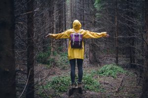 A woman wears a rain jacket in the woods with her arms held out. She is feeling in control after beginning anxiety therapy in Colorado Springs, CO with Altitude Counseling. Her anxiety therapist for online therapy in Colorado is highly trained and has provided her with the anxiety support she needs.