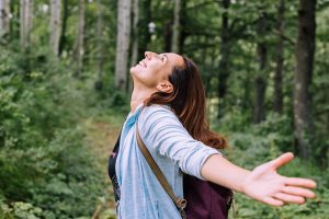 A woman smiles in the woods with her arms extended. She is feeling happy after starting online therapy in CO with Altitude Counseling in Colorado Springs, CO. An online therapist can help you with trauma therapy and emdr therapist in colorado springs, co
