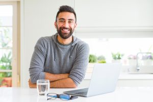 A man smiles while using his laptop. He is feeling happy after starting online therapy in Colorado with Altitude Counseling in Colorado Springs, CO.
