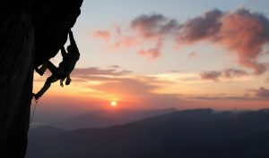A male climbs the side of a mountain after PTSD Treatment in Colorado Springs, CO. He is feeling better after beginning trauma therapy in Colorado Springs, CO with Altitude Counseling. He can get help in Parker, CO from a trauma therapist too.