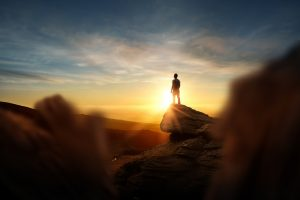 A person stands on top of a cliff feeling empowered. They are happy after starting depression counseling in Colorado Springs, CO with Altitude Counseling. 80918 Contact us for online therapy in Colorado too!