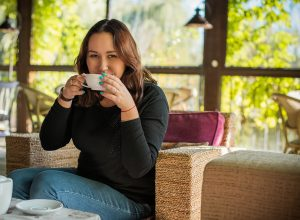 A woman smiles while drinking a cup of coffee. She is feeling happy after starting depression counseling in Colorado Springs, CO with Altitude Counseling. 80918