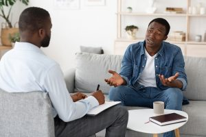 A man sits in a counseling session. He is feeling better since starting therapy for men in Colorado Springs, CO with Altitude Counseling. 80918