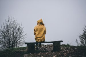 A person sits on a bench alone. They are having a hard time with symptoms of grief in Colorado. They are looking forward to starting grief counseling in Colorado with Altitude Counseling.