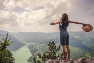 A woman stands on a mountain no longer feeling symptoms of grief in Colorado. She is happy she started grief counseling in Colorado with Altitude Counseling.