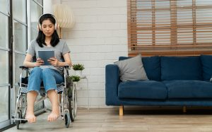 A person in a wheelchair uses an ipad. They represent someone looking to start individual therapy in Colorado Springs, CO with Altitude Counseling.